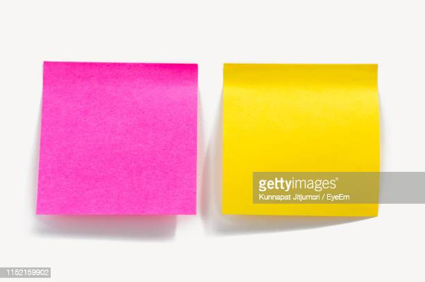 close-up of yellow and pink adhesive notes on white background - adhesive note stock pictures, royalty-free photos & images
