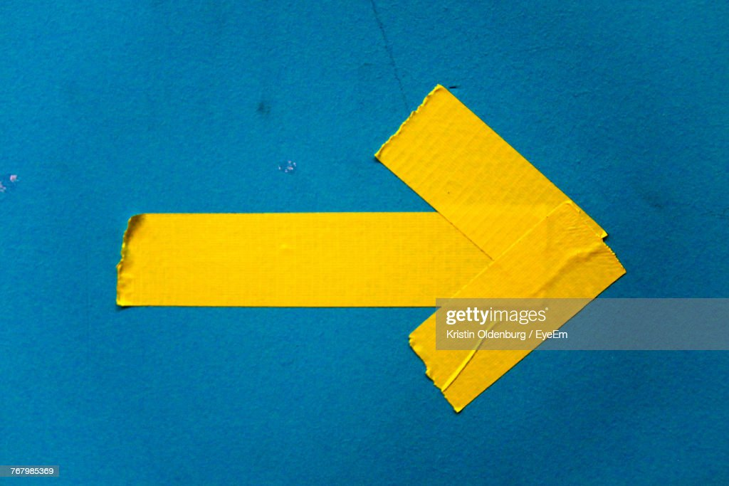 Close-Up Of Yellow Arrow Symbol On Blue Wall : Stock Photo