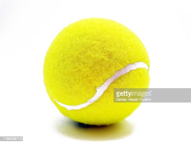 close-up of yellow ball against white background - tennis ball stock pictures, royalty-free photos & images
