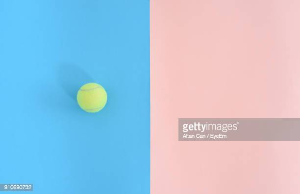 close-up of yellow ball over colored background - tennis ball stock pictures, royalty-free photos & images