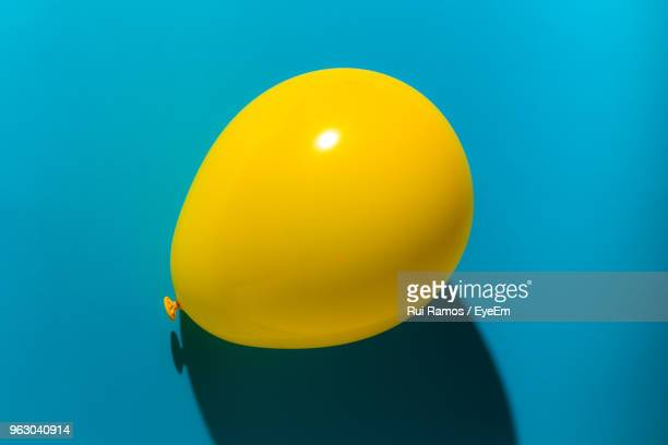 Close-Up Of Yellow Balloon Over Blue Background