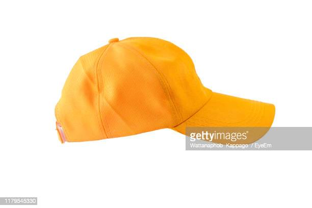 close-up of yellow cap against white background - yellow hat stock pictures, royalty-free photos & images