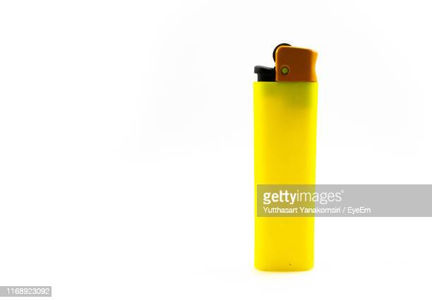 close-up of yellow cigarette lighter against white background - cigarette lighter stock pictures, royalty-free photos & images