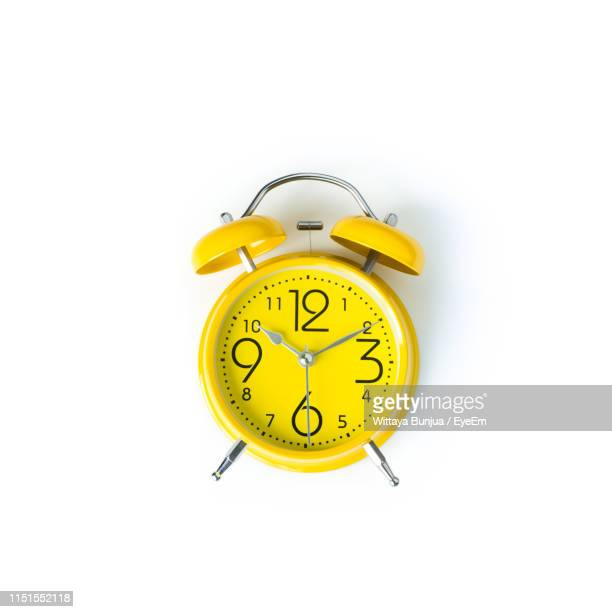 close-up of yellow clock over white background - alarm clock stock pictures, royalty-free photos & images