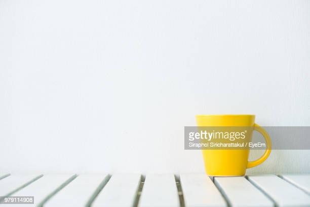 close-up of yellow cup on table against white background - yellow photos et images de collection