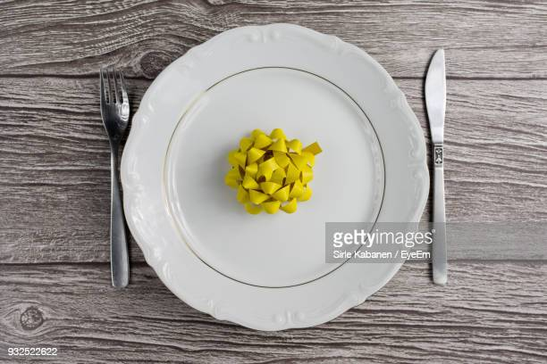 Close-Up Of Yellow Decoration In Plate On Wooden Table
