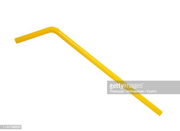 close-up of yellow drinking straw against white background - drinking straw stock pictures, royalty-free photos & images