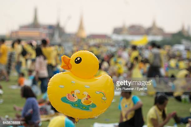 Close-Up Of Yellow Duck Balloon With People At Wat Phra Kaew