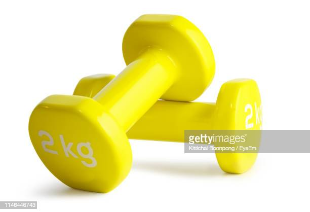close-up of yellow dumbbells over white background - dumbbell stock pictures, royalty-free photos & images