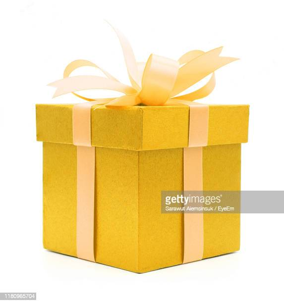 close-up of yellow gift against white background - gift box stock pictures, royalty-free photos & images
