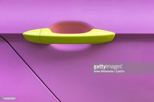 Close-Up Of Yellow Handle On Pink Car