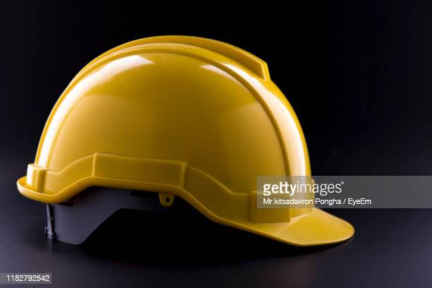 close-up of yellow hardhat against black background - work helmet stock pictures, royalty-free photos & images