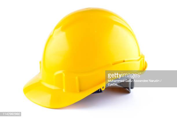 close-up of yellow hardhat against white background - schutzhelm stock-fotos und bilder