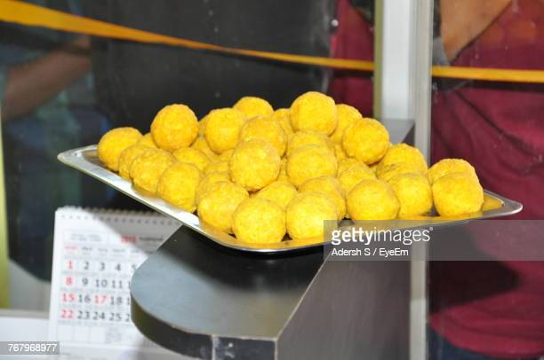 Close-Up Of Yellow Laddoos In Tray