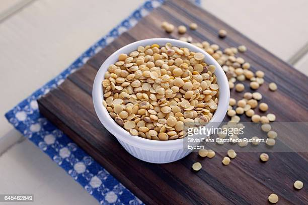 Close-Up Of Yellow Lentils In Bowl On Cutting Board