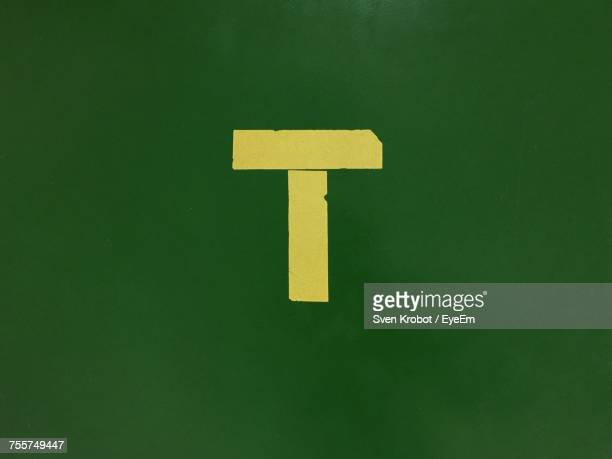 Close-Up Of Yellow Letter T On Green Wall