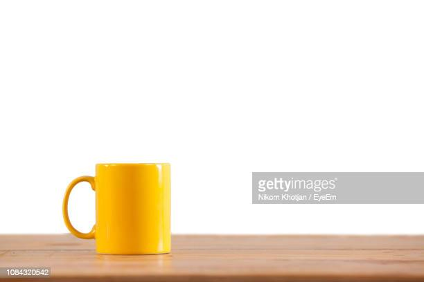 close-up of yellow mug on table against white background - mug stock pictures, royalty-free photos & images