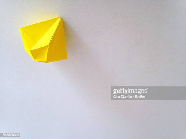 Close-Up Of Yellow Origami Pattern Stuck On White Wall