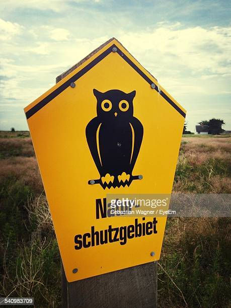 Close-Up Of Yellow Owl Sign Board On Field
