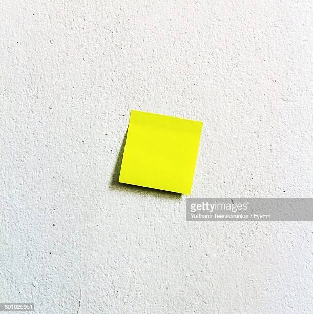 Close-Up Of Yellow Paper Stuck On White Wall