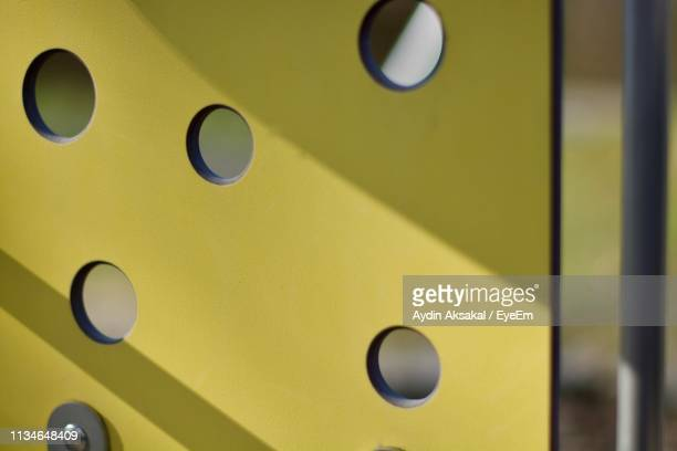 Close-Up Of Yellow Partition With Holes