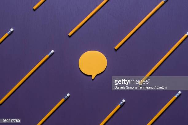 Close-Up Of Yellow Pencils And Speech Bubbles On Purple Table