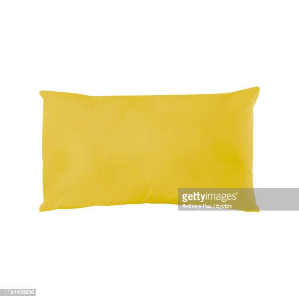 close-up of yellow pillow against white background - pillow stock pictures, royalty-free photos & images