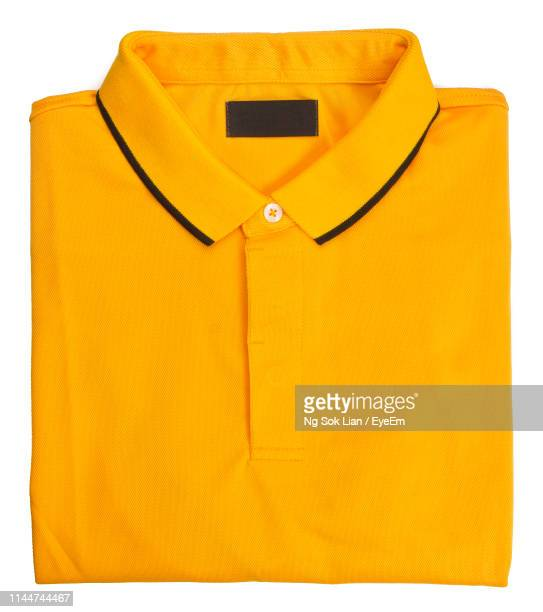 close-up of yellow polo shirt against white background - ポロシャツ ストックフォトと画像