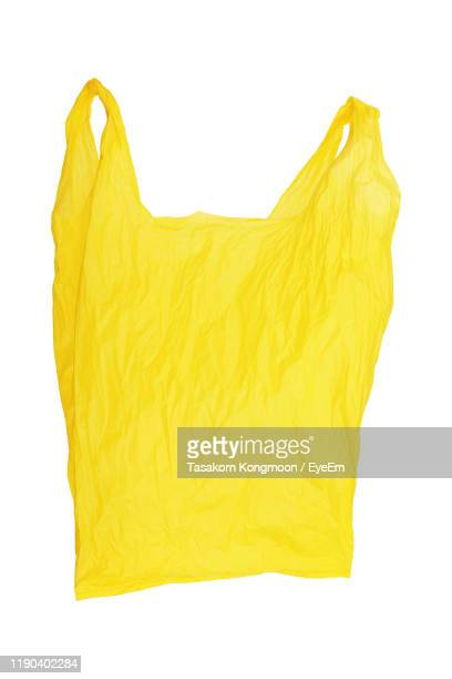 close-up of yellow polythene bag against white background - ビニール袋 ストックフォトと画像