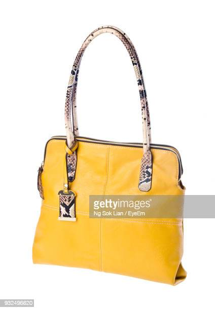 Close-Up Of Yellow Purse Over White Background