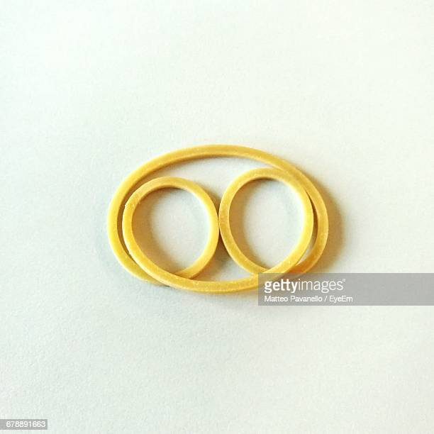 close-up of yellow rubber band against white background - gummi stock-fotos und bilder