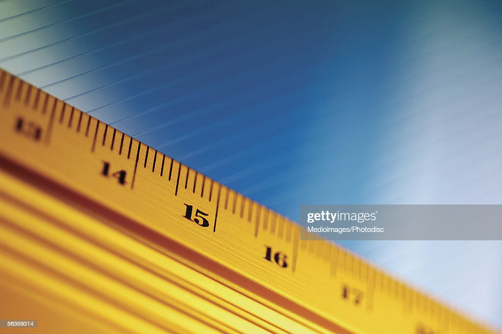 Close-up of yellow ruler against blue and white background : Stock Photo