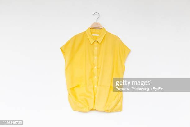 close-up of yellow shirt over white background - all shirts photos et images de collection