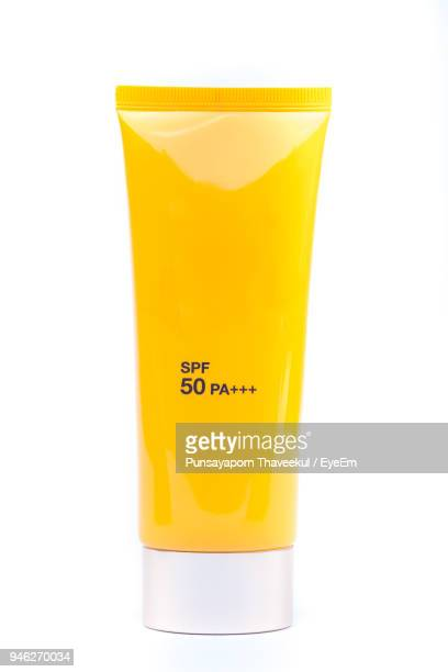 close-up of yellow suntan lotion against white background - sunscreen stock photos and pictures