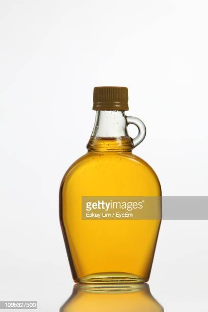 close-up of yellow syrup in bottle against white background - syrup stock pictures, royalty-free photos & images
