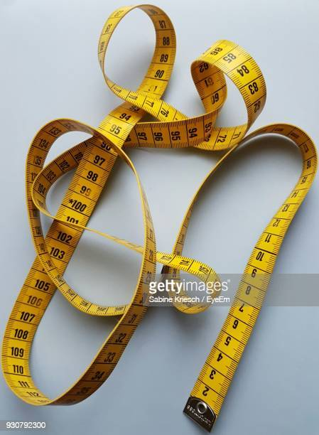 Close-Up Of Yellow Tape Measure Over White Background