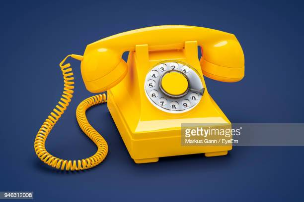 Close-Up Of Yellow Telephone On Blue Background