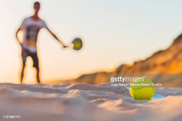 Close-Up Of Yellow Tennis Ball On Sand At Beach Against Sky During Sunset