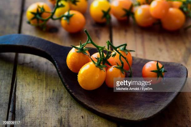 Close-Up Of Yellow Tomatoes On Wooden Spatula