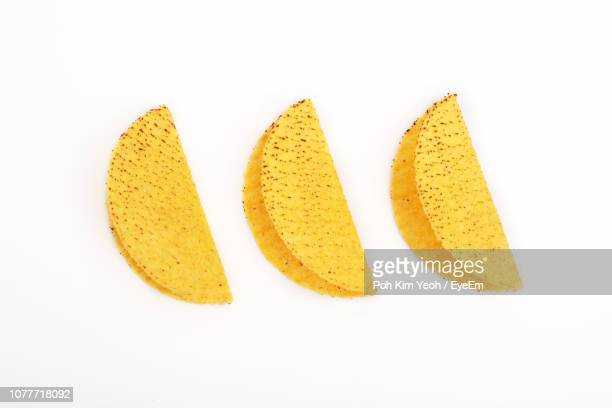 close-up of yellow tortillas against white background - tortilla flatbread stock photos and pictures