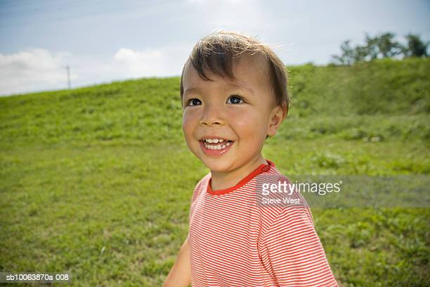 Close-up of young boy (2-3) on hill, smiling