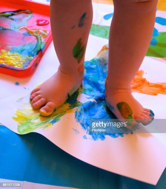 Close-up of young child creating foot prints with coloured paint