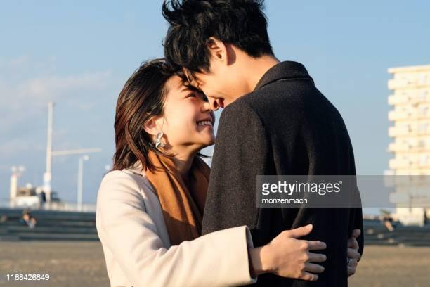 ビーチで抱き合う若いカップルのクローズアップ - カップル ストックフォトと画像