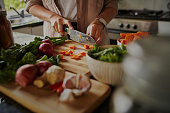 Closeup of young female hands chopping fresh vegetables on chopping board while in modern kitchen - preparing a healthy meal to boost immune system and fight off coronavirus