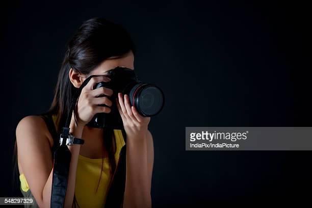 close-up of young female photographer taking a photograph - photographe professionnel photos et images de collection