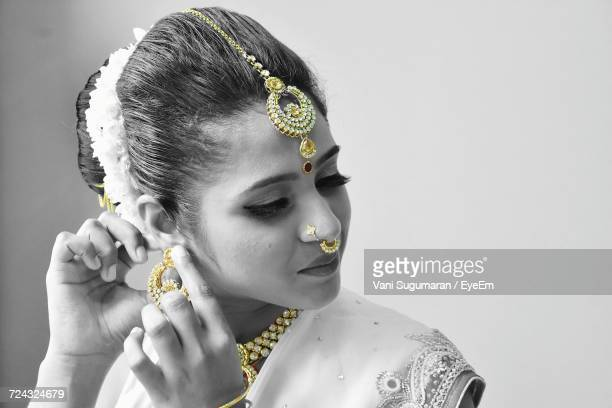 Close-Up Of Young Indian Woman Wearing Jewelry Against Gray Background