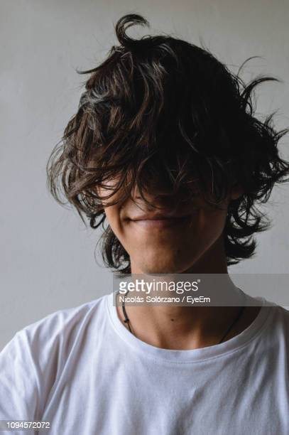 close-up of young man against wall - bad hair stock pictures, royalty-free photos & images
