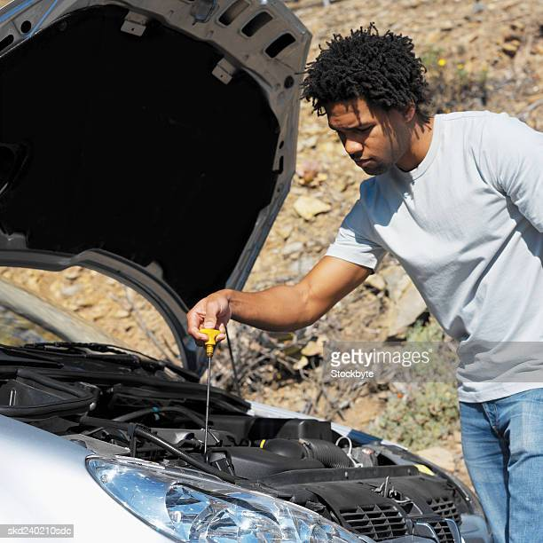 Close-up of young man checking oil level of car with dipstick