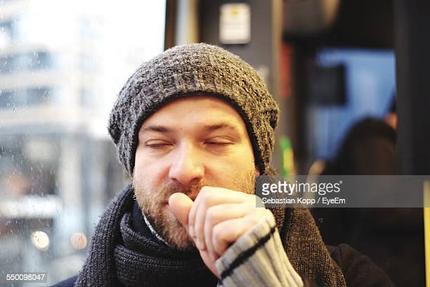 close-up of young man coughing in bus - cough stock photos and pictures