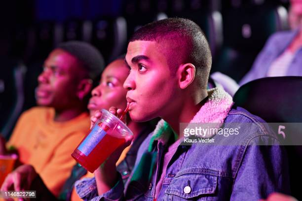 Close-up of young man drinking soda while watching movie in cinema hall